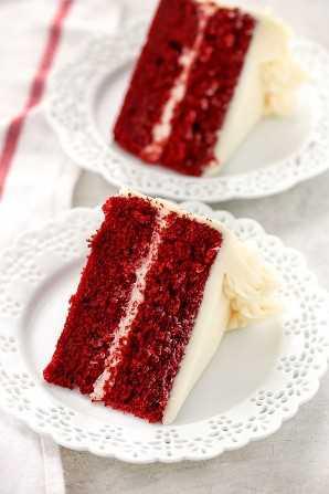 Dos rebanadas de pastel de terciopelo rojo cubierto con queso crema frosting en platos decorativos blancos y una servilleta blanca en el lateral.