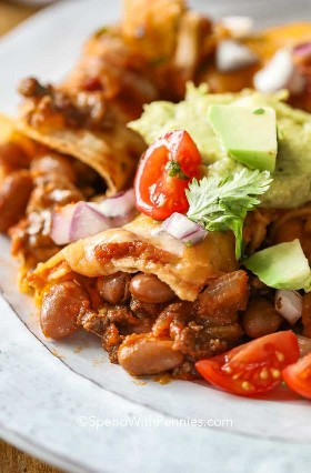 En un plato con enchiladas de carne molida con cilantro, guacamole y tomates.