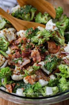 Un cierre para arriba de la ensalada de la coliflor del bróculi por completo del tocino con las cucharas de la porción.