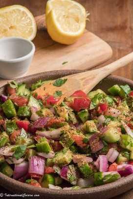 un tazón de tomates picados, pepino, cebolla todo mezclado con menta y cilantro, ensalada Kachumber