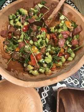 un tazón lleno de fresco picado, tomates, chalotes, pepino, aguacate y atún fresco, una colorida ensalada de poke