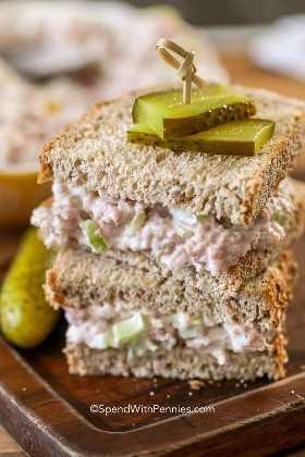 Un sándwich de ensalada de jamón cortado por la mitad con un pepinillo encima.