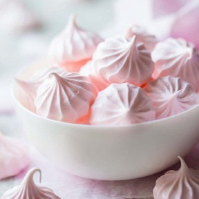 Besos de merengue rosa pálido en un tazón blanco.
