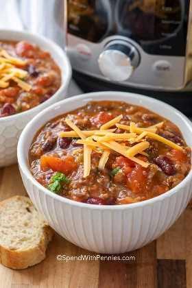 Dos tazones de chile Instant Pot cubiertos con queso con un Instant Pot en el fondo y una rebanada de baguette al lado.