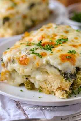 Una rebanada de lasaña de pollo con queso en un plato blanco cubierto con perejil fresco.