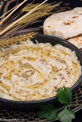 un tazón cremoso de liebre qatari que está rociado con ghee y semillas de cilantro.