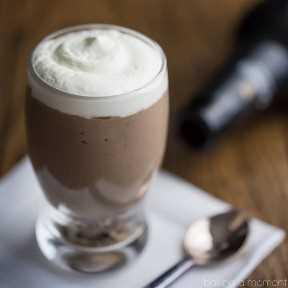 Mini vaso de cerveza de mousse de chocolate Guinness, en una servilleta blanca con una cuchara y una botella de Guinness Stout al fondo