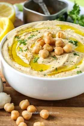 Un tazón de hummus lleno de deliciosos ingredientes como ajo, garbanzos, tahini y otras especias.