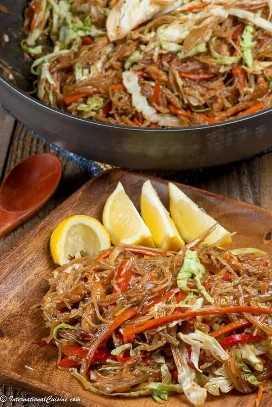 Un plato de fideos pancit con cerdo y verduras.