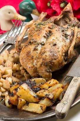 Um pato assado inteiro em uma bandeja com maçãs e batatas crocantes.