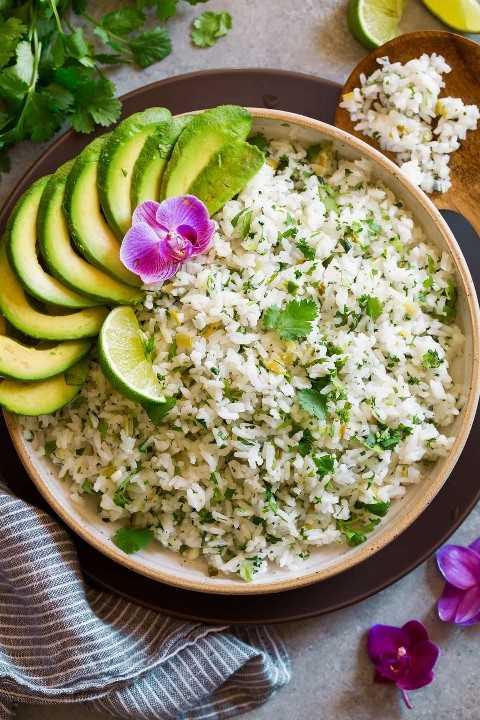 Arroz con limón y cilantro en un tazón de cerámica de color crema sobre un plato marrón mate. El arroz está adornado con cilantro, lima, aguacate y flor de orquídea.