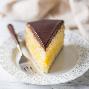 Una rebanada de Boston Cream Pie con un pastel de vainilla húmedo emparedado con un rico relleno de crema de pastelería y una cobertura de glaseado de chocolate brillante.