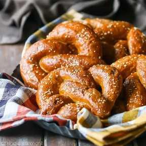 Abundante canasta llena de suaves pretzels marrones bruñidos, acurrucados en una servilleta a cuadros naranja.