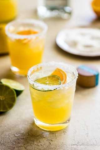 Copa de cóctel margarita flaco adornada con rodajas de limón y naranja.