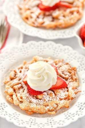 Dos pasteles de embudo con azúcar en polvo, fresas y crema batida casera sobre platos decorativos blancos.