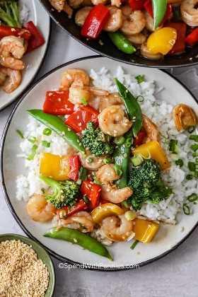 Un tiro por encima de camarones salteado en una cama de arroz en un plato blanco.