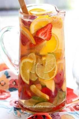 Una jarra de sangría blanca con fruta.
