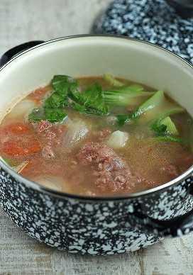 Sinigang de carne en conserva en una olla para sopa en blanco y negro