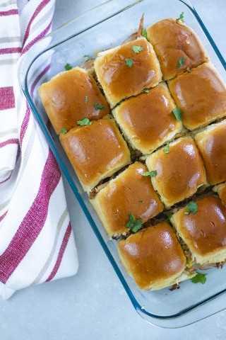 Los Sliders cubanos están llenos de jamón dulce, queso suizo, cerdo asado, pepinillos y mostaza. - Pequeña galleta inteligente