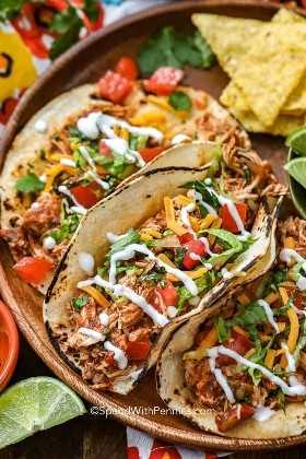 En una bandeja de madera, se sirven tacos de ollas y se sirven en tortillas con queso, lechuga, crema agria y tomates.