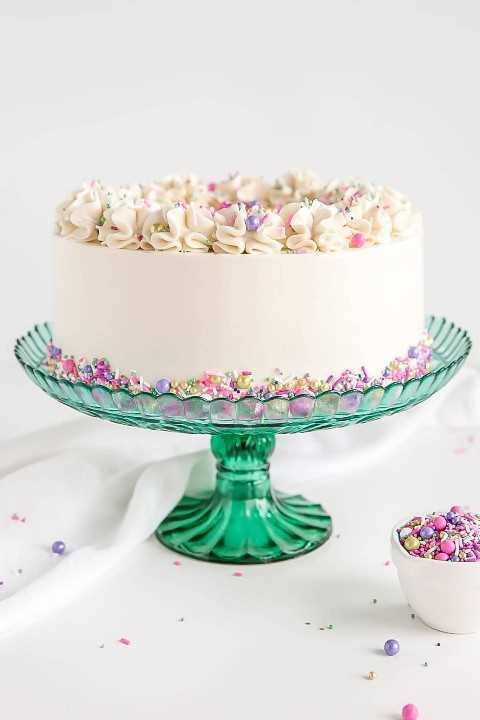 Receta de pastel blanco con crema de merengue suizo blanco y espolvoreado.