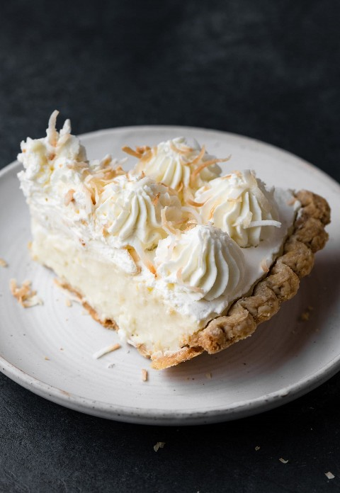 Rebanada de pastel de crema de coco en un plato blanco sobre una mesa gris oscuro.