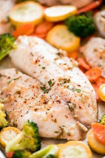 ¡Esta Tilapia al horno y verduras asadas es un plato bajo en calorías y alto en proteínas que se reúne en menos de 25 minutos!