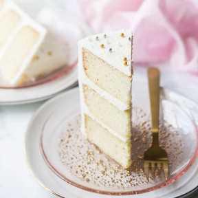 Rebanada de la capa triple de la torta blanca de la crema agria de la almendra en una placa rosada.
