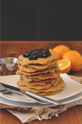 Pila de nuestros deliciosos pasteles de plancha de trigo integral cubiertos con compota de naranja de arándanos