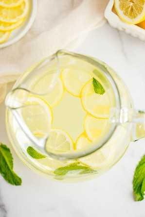 Una jarra grande de vidrio llena de limonada casera, rodajas de limón y hojas de menta fresca.