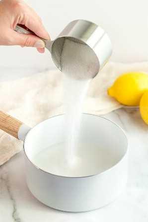 Una mano agregando una taza de azúcar a una cacerola llena de agua.