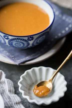 Uma colher de sopa de doce de leite em um pequeno prato branco, com uma tigela maior de doce de leite em segundo plano.