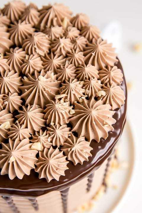 Ciérrese para arriba de la tubería encima de una torta de Nutella del chocolate.