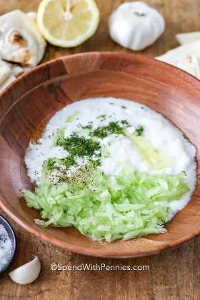 Los ingredientes para tzatziki se sumergen en un tazón de madera listo para mezclar.