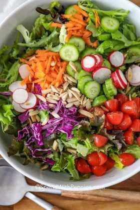 Un plato de ensalada tirada con zanahorias, pepinos, tomates y rábanos.