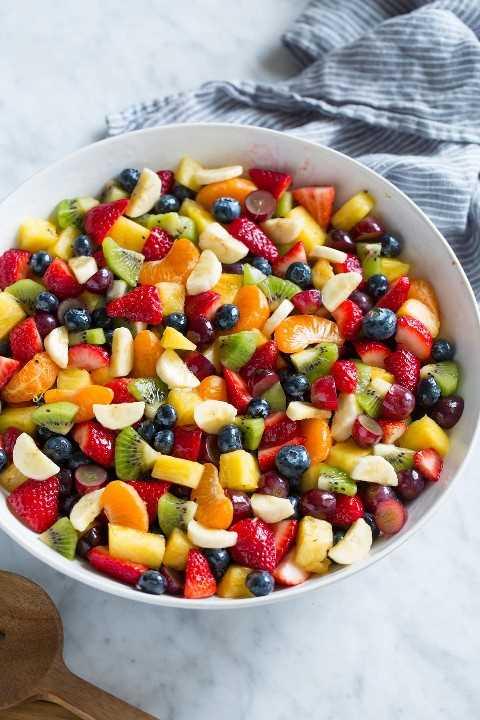 Ensalada de frutas con fruta fresca picada en un tazón grande para ensaladas sobre una superficie de mármol.