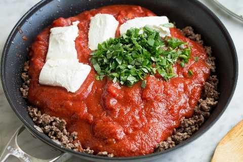 Agregue la salsa marinara, el queso crema y la albahaca fresca a la carne molida en una sartén.