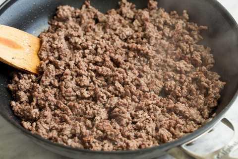 Dorar la carne molida en una sartén para salsa de espagueti.