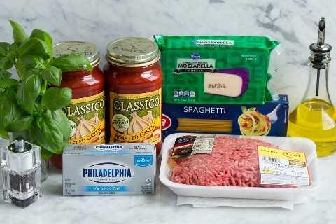 Aquí se muestran los ingredientes de espagueti al horno, que incluyen espaguetis, carne molida, salsa marinara, queso crema claro, albahaca fresca, mozzarella y aceite de oliva.