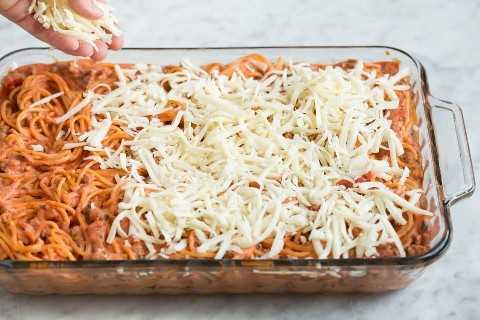 Agregar queso a la cazuela de espagueti al horno.