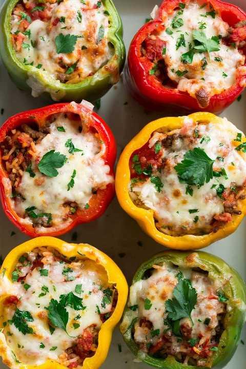 Ciérrese encima de la imagen de arriba de pimientas rellenas en un plato de la hornada.