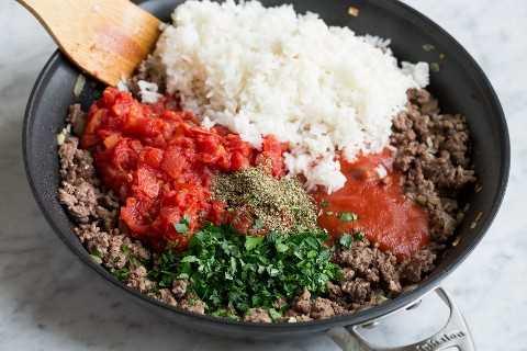 Agregue arroz cocido, tomates, salsa de tomate y hierbas a la mezcla de carne molida en una sartén.