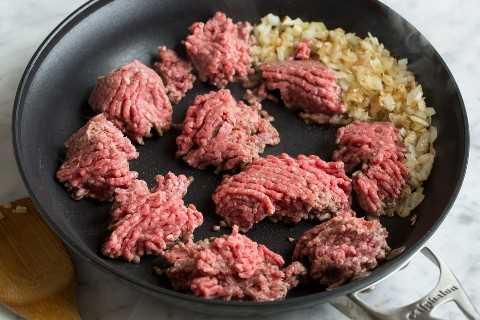 Mostrar cómo hacer pimientos rellenos, dorar la carne molida en una sartén junto con cebollas amarillas.
