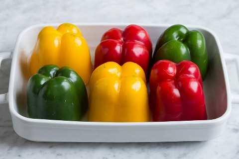 6 pimientos multicolores en una fuente de horno blanco.