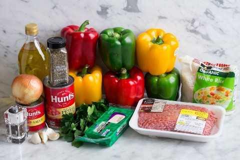 Aquí se muestran ingredientes para hacer pimientos rellenos, que incluyen pimientos, carne molida, salsa de tomate, tomates picados, ajo, cebolla, condimento italiano, mozzarella, arroz blanco, aceite de oliva, perejil.
