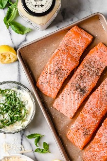 ¡Estoy obsesionada con esta receta de salmón con freidoras de albahaca y parmesano! Hacer salmón en la freidora es rápido y fácil, y el pescado sale jugoso por dentro.