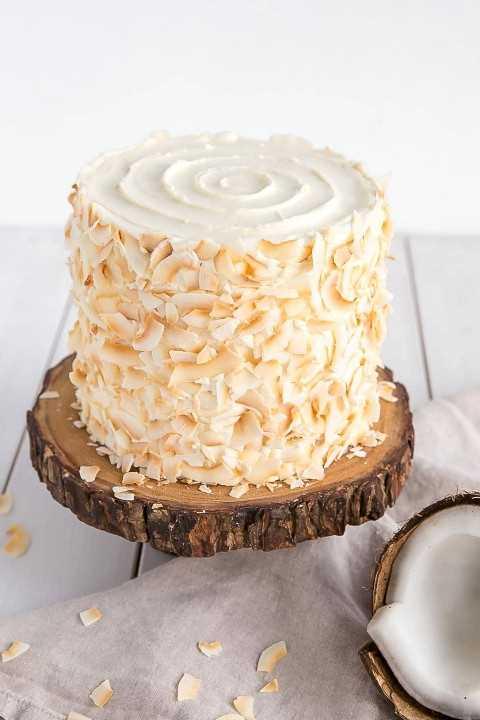 Pastel de coco hecho en casa decorado con coco tostado y un remolino de glaseado en la parte superior.
