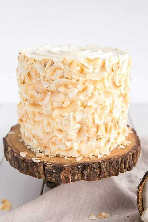 Copos de coco tostado decoran el exterior de este pastel de coco.