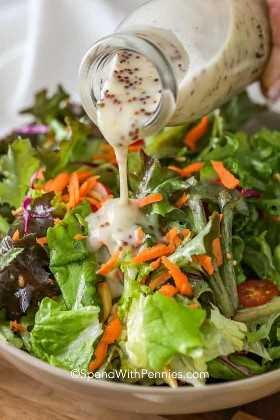 El aderezo de mostaza hecho en casa se vierte sobre una ensalada