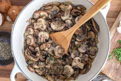 Una olla de champiñones fritos listos para hacer crema de champiñones.